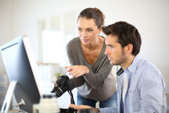 Photo reporters working on computer. Photo reporters working in office Royalty Free Stock Photography