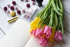 A bouquet of tulips, a note book, some jewellery, eye shadows, sweets, palette. A photo representing a an ideal spring woman day - a bouquet of tulips, a note Stock Photos