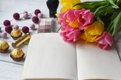 A bouquet of tulips, a note book, some jewellery, eye shadows, sweets, palette. A photo representing a an ideal spring woman day - a bouquet of tulips, a note Stock Photography