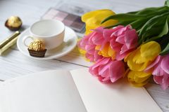 A bouquet of tulips, a cup of tea, some sweets, a note book, some jewellery, eye. A photo representing a spring concept for women - a bouquet of tulips, a cup of Royalty Free Stock Image