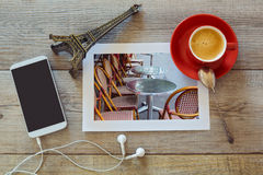 Photo of restaurant in Paris on wooden table with coffee cup and smart phone. View from above. Photo of restaurant in Paris on wooden table with coffee cup and Royalty Free Stock Images