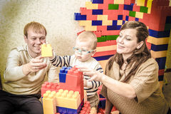 Photo in retro style of young parents and little son building Stock Photography