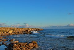 Photo rocky shore of the lake in the early morning, with waves and clouds on the horizon. royalty free illustration