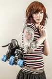 Beautiful roller derby woman holding skates. Photo of a roller derby girl holding her skates by the laces Royalty Free Stock Image