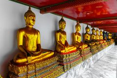 Row of golden buddhas in the Temple of the Reclining Buddha, Bangkok, Thailand royalty free stock photo