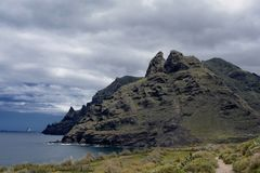 Photo of a rugged mountain jutting into the sea. Photograph of the edge of a volcanic mountain range jutting into the ocean, North Tenerife Stock Photos