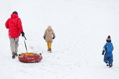 Photo of running father with tubing, son and daughter on winter park royalty free stock image