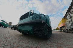 Photo of a Russian green armored car on a caterpillar track among the railway trains. Strong distortion from the fisheye len. S stock photos