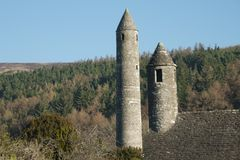 Ancient Twin Towers of Glendalough. This photo`s angle is a little deceptive. The tallest tower is the renouned round tower of Glendalough. The 2nd tower is part stock photos