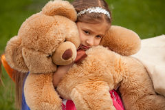 Photo of sad little girl hugging teddy bear Stock Photo