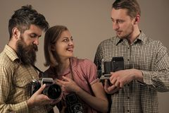 Photo salon. Friendship. Fashion Photographer with old film camera in hand while working in studio. Vintage dressed royalty free stock photography