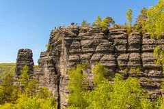 Sandstone rock tower in the summer valley of national park Bohemian Switzerland. A photo of a sandstone rock tower in the deep summer valley of national park royalty free stock photography
