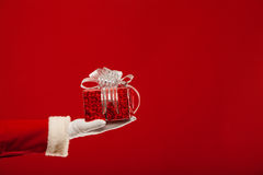 Photo of Santa Claus gloved hand with  giftbox, on Stock Photo