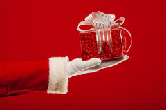 Photo of Santa Claus gloved hand with  giftbox, on Stock Images