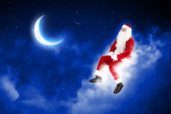 Photo of santa claus sitting on the moon Stock Photos