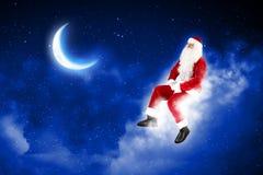 Photo of santa claus sitting on the moon Stock Photos
