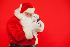 Photo of Santa Claus using mobile phone, on a red background. Ch. Ristmas stock image