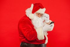 Photo of Santa Claus using mobile phone, on a red background. Ch. Ristmas stock photos