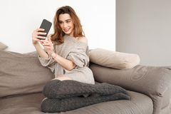 Photo of satisfied woman with brown hair sitting on couch in apartment, and taking selfie on cell phone. Photo of satisfied woman with brown hair sitting on royalty free stock images