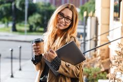 Photo of satisfied woman 20s holding laptop while walking through city street. Photo of satisfied woman 20s holding laptop and drinking takeaway coffee while stock images