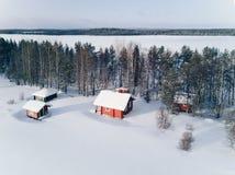 Photo scénique d'hiver d'un cottage près du lac et des arbres couverts dans la neige Photo stock