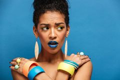 Photo of scared or agitated mulatto woman with colorful makeup a. Nd fashion accessories looking aside with crossed hands on shoulders over blue wall Stock Photo