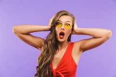 Photo of scared or shocked woman 20s wearing red dress and sunglasses screaming and covering ears with hands, standing isolated o stock images