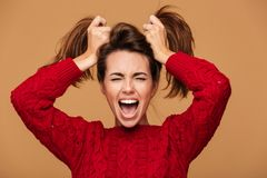 Photo of screaming brunette woman with closed eyes making two po Royalty Free Stock Photos
