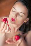 Photo of seductive female eating strawberry, closeup portrait re Stock Photography