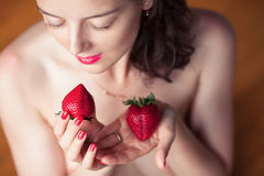 Photo of seductive female eating strawberry, closeup portrait redhead sensual woman biting berry Stock Photos