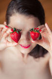 Photo of seductive female holding strawberry near face eyeys, cl Royalty Free Stock Photography