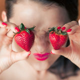 Photo of seductive female holding strawberry near face eyeys, closeup portrait redhead sensual woman biting berry Royalty Free Stock Images