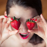 Photo of seductive female holding strawberry near face eyeys, closeup portrait redhead sensual woman biting berry Stock Photos