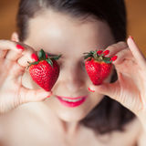 Photo of seductive female holding strawberry near face eyeys, closeup portrait redhead sensual woman biting berry Royalty Free Stock Photos
