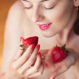 Photo of seductive female holding strawberry near face eyeys, closeup portrait redhead sensual woman biting berry Stock Photography
