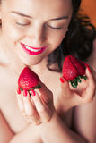Photo of seductive female holding strawberry near face lips, clo Royalty Free Stock Photography
