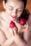 Photo of seductive female holding strawberry near face lips, clo Royalty Free Stock Images