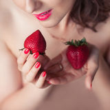Photo of seductive female holding strawberry near face lips, clo Stock Photo