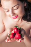 Photo of seductive female holding strawberry near face lips, clo Stock Images
