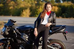 Photo of self assured woman dressed in leather jacket, black trousers, leans on motorbike, has thoughtful expression, rests after. Long journey, has good rest stock image