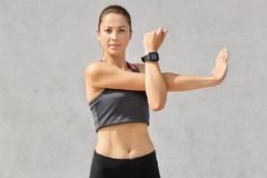 Photo of self confident female stretches hands, warms up before training, has sporty body, wears smartwatch, casual top and leggin stock image