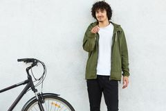 Photo of self confident male has curly hair, dressed in fashionable anorak, points with index finger directly at camera, makes cho. Ice, asks you to ride bicycle stock image