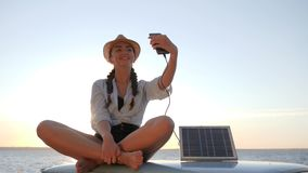 Photo selfie on vehicle, girl sits on roof retro car in backlight makes selfie on phone, young woman using powered solar stock video