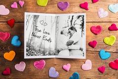 Photo of senior couple in love, colorful fabric hearts. Studio s Stock Photo