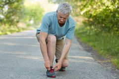 Photo of senior male has running exercise outdoor, laces sneakers on road, takes break after jogging, dressed casually, poses in c. Ountryside background Royalty Free Stock Photography