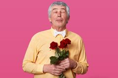 Photo of senior man with bouquet of red flowers, keeps eyes closed, lips folded, dressed in yellow shirt with white bowtie, waits stock photo