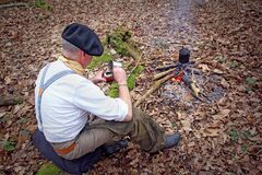 Senior active man camping in woods with yerba drink