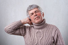 A photo of senior man wearing glasses being tired from hard work holding his hand on head. A mature man having headache after work Royalty Free Stock Photography