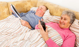 Senior man reading and his wife surfing the internet Royalty Free Stock Images