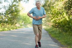 Photo of senior wrinkled male touches stomach, has pain after covering long distance during morning run, dressed in sportswear, ha. S athletic body, joggs in Royalty Free Stock Images